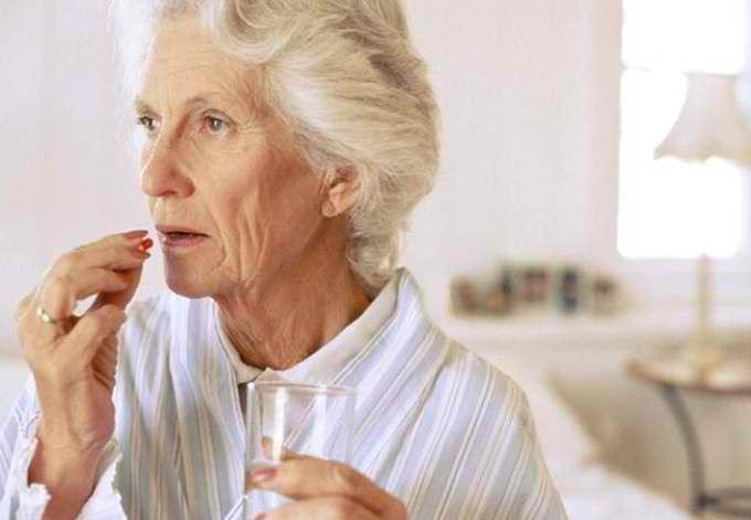 Старушка пьет таблетки